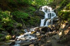 美丽的瀑布在森林里从一个巨大的岩石出来 免版税库存图片
