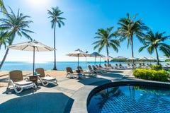 美丽的热带海滩和海有伞的和椅子在游泳场附近 免版税库存图片