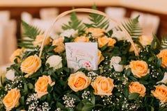 美丽的玫瑰花束与明信片的在一张白色木桌上 衣物夫妇日愉快的葡萄酒婚礼 库存照片