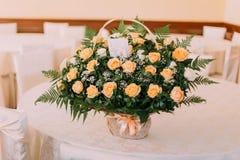 美丽的玫瑰花束在一张白色木桌上的 衣物夫妇日愉快的葡萄酒婚礼 图库摄影