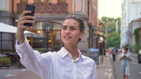 美丽的现代妇女在街道上在智能手机站立并且做selfie自白天,微笑,通信概念 股票视频