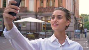 美丽的现代妇女在街道上在智能手机站立并且做selfie,微笑,通信概念,都市 股票视频
