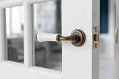 美丽的现代门把手 从一个高级家的内部的开放,木前门有窗口的 图库摄影