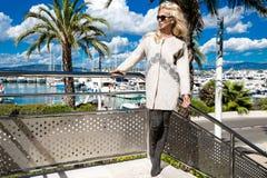 美丽的现象惊人的典雅的豪华性感的白肤金发的式样妇女穿外套和起动的和在游艇的太阳镜立场 免版税库存照片