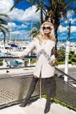 美丽的现象惊人的典雅的豪华性感的白肤金发的式样妇女穿外套和起动的和在游艇的太阳镜立场 库存图片