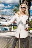 美丽的现象惊人的典雅的豪华性感的白肤金发的式样妇女穿外套和起动的和在游艇的太阳镜立场 免版税库存图片