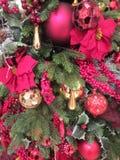 美丽的球、红色花和其他明亮地色的装饰品在圣诞树 库存照片