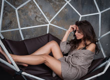 美丽的甜逗人喜爱的深色的妇女女孩画象偶然行家温暖的灰色毛线衣的穿衣,坐 库存照片