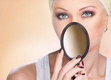 美丽的由小镜子的妇女闭合值的面孔画象  库存照片
