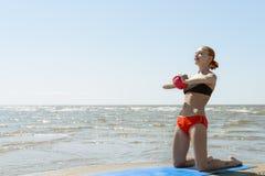 美丽的由海运的妇女实践的健身 免版税库存图片