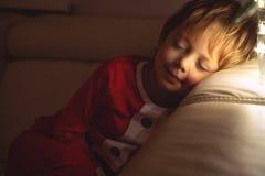 美丽的男孩在沙发睡觉在圣诞夜 睡觉在圣诞树下的孩子 免版税库存图片