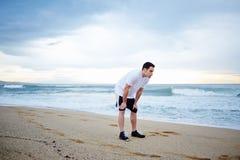 美丽的男性运动员在站立在沙子的白色T恤杉穿戴了休息在密集的早晨凹凸部以后 库存图片