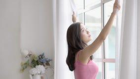 美丽的画象年轻亚裔妇女放松开放帷幕在看外面在卧室的窗口早晨 股票录像