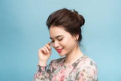 美丽的画象年轻亚裔妇女确信认为在蓝色背景 图库摄影
