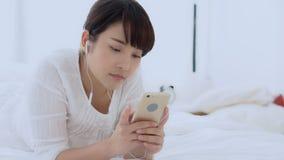 美丽的画象年轻亚裔妇女说谎的愉快的耳机听的音乐与在卧室,女孩乐趣耳机放松并且享用 股票视频