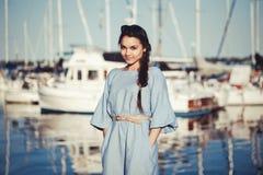 美丽的白白种人深色的妇女画象有被晒黑的皮肤的在蓝色礼服,由湖岸海滨 图库摄影