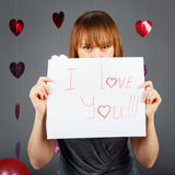 美丽的白白种人白肤金发的红发女孩妇女在有红色心脏的演播室在拿着一张纸的灰色背景 库存图片