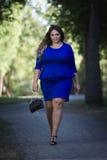 年轻美丽的白种人加上大小在户外蓝色礼服的时装模特儿,自然的xxl妇女 免版税库存图片
