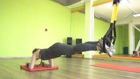 美丽的白种人女孩专业教练员执行在铰链TRX的困难的锻炼 影视素材
