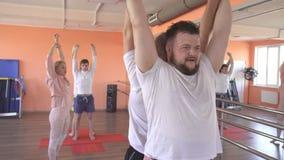 美丽的白种人女性辅导员在一个男性小组会议上教瑜伽技术 加强肌肉和健康 影视素材