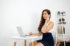 美丽的白种人妇女谈话在电话,当使用在白色书桌上的膝上型计算机在有拷贝空间的时干净的家庭办公室 免版税库存照片