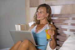 美丽的白种人妇女30s坐床在晚上在家庭卧室使用互联网在喝健康橙色ju的便携式计算机 免版税库存照片