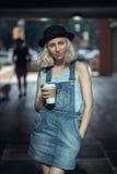 美丽的白种人少年年轻白肤金发的备选模型女孩妇女画象蓝色T恤杉的,看在照相机h的牛仔裤连裤外衣 库存图片