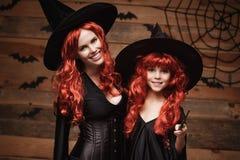 美丽的白种人有长的红色头发的在巫婆服装和不可思议的鞭子庆祝万圣夜的母亲和她的女儿 免版税库存图片