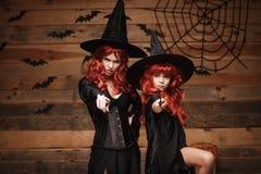 美丽的白种人有长的红色头发的在巫婆服装和不可思议的鞭子庆祝万圣夜的母亲和她的女儿 库存图片