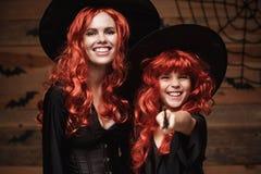 美丽的白种人有长的红色头发的在巫婆服装和不可思议的鞭子庆祝万圣夜的母亲和她的女儿 图库摄影