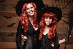 美丽的白种人有长的红色头发的在巫婆服装庆祝万圣夜的母亲和她的女儿摆在与  免版税库存图片
