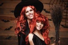 美丽的白种人有长的红色头发的在巫婆服装庆祝万圣夜的母亲和她的女儿摆在与  库存图片