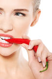 美丽的白种人露胸部的妇女用在嘴的辣椒。 免版税库存照片