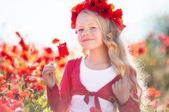 美丽的白肤金发的儿童女孩在鸦片草甸佩带从红色花的花圈 免版税库存照片