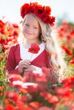 美丽的白肤金发的儿童女孩在鸦片草甸,春天佩带从红色花的花圈 库存图片
