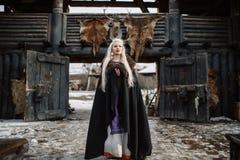 美丽的白肤金发的北欧海盗在一个黑斗篷穿戴了 免版税库存照片