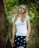 美丽的白肤金发的十几岁的女孩外面在森林 库存照片