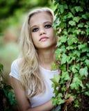美丽的白肤金发的十几岁的女孩外面在森林 免版税库存图片