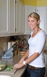 美丽的白肤金发的厨房妇女 免版税库存图片