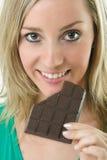 美丽的白肤金发的吃的妇女 免版税库存图片