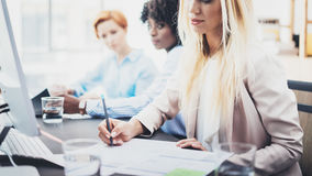 美丽的白肤金发的在工作场所的妇女签署的文件在办公室 小组一起谈论女孩的工友企业项目 贺尔 免版税库存图片