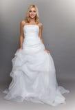 美丽的白肤金发的在灰色的新娘白色长的婚礼礼服 免版税库存图片