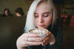 年轻美丽的白肤金发的女孩享用一个杯子可可粉用蛋白软糖和一个舒适咖啡馆 免版税库存图片