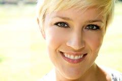 美丽的白肤金发的女孩俏丽的微笑 免版税库存图片