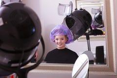 美丽的白肤金发的女孩卷发夹路辗美发师美容院 库存图片