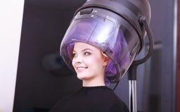 美丽的白肤金发的女孩卷发夹路辗美发师美容院 库存照片