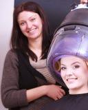美丽的白肤金发的女孩卷发夹路辗美发师美容院 免版税库存照片
