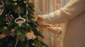 美丽的白肤金发的女孩在一个舒适晚上房子里装饰一棵圣诞树 股票录像