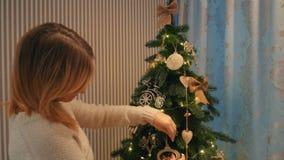 美丽的白肤金发的女孩在一个舒适晚上房子里装饰一棵圣诞树 影视素材