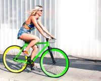 美丽的白肤金发的女孩在一辆陡峭的绿色固定的自行车乘坐在欧洲城市公园  图库摄影